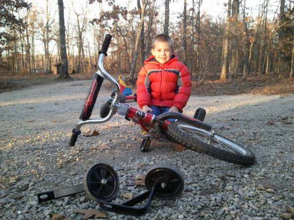 "Jackson sits proudly with his ""new"" bike, without training wheels."