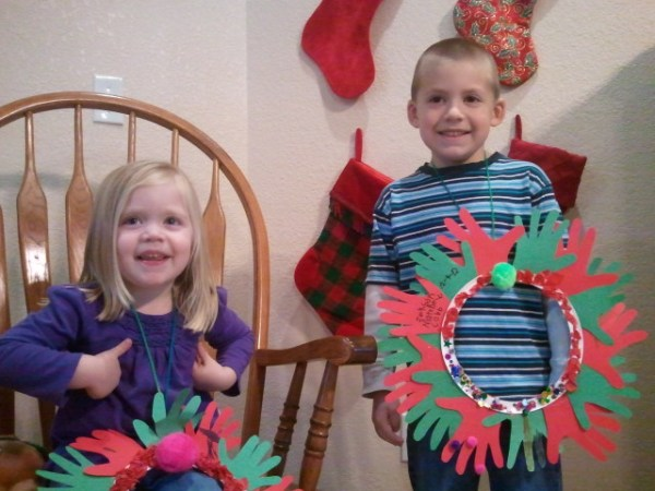Lauren and Jackson display their unique wreaths, made of their hand prints.