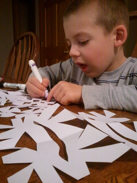 Jackson decorates his paper snowflakes.