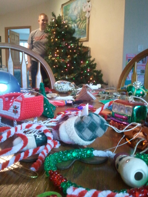 Matt holds up the broken tree, while I take off the ornaments and place them on a nearby table.