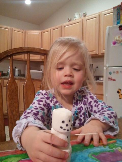 Lauren eyeing her marshmallow snowman