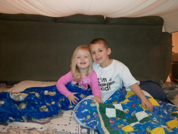 The kids settle in under the blanket fort for family movie night.