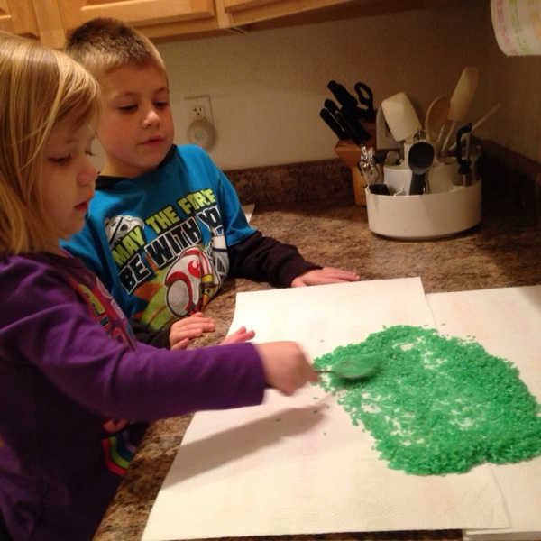 Lauren spreads our her green rice to dry while Jackson watches.