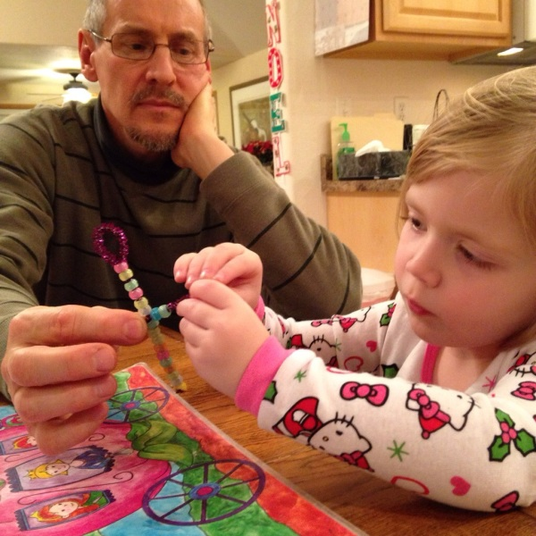 Papa helps Lauren make her cross ornament.