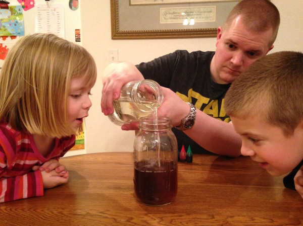 Jackson and Lauren watch as the water filled with sin (food coloring drops) becomes clean when the Jesus jar is poured in.