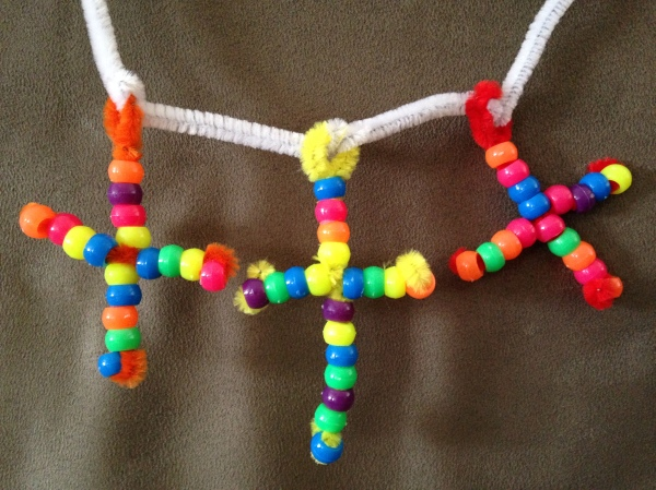 A close-up of the Three Cross Bead Necklace. This simple craft project is easy to modify and great for young toddlers with supervision or grade schoolers who want to be creative.