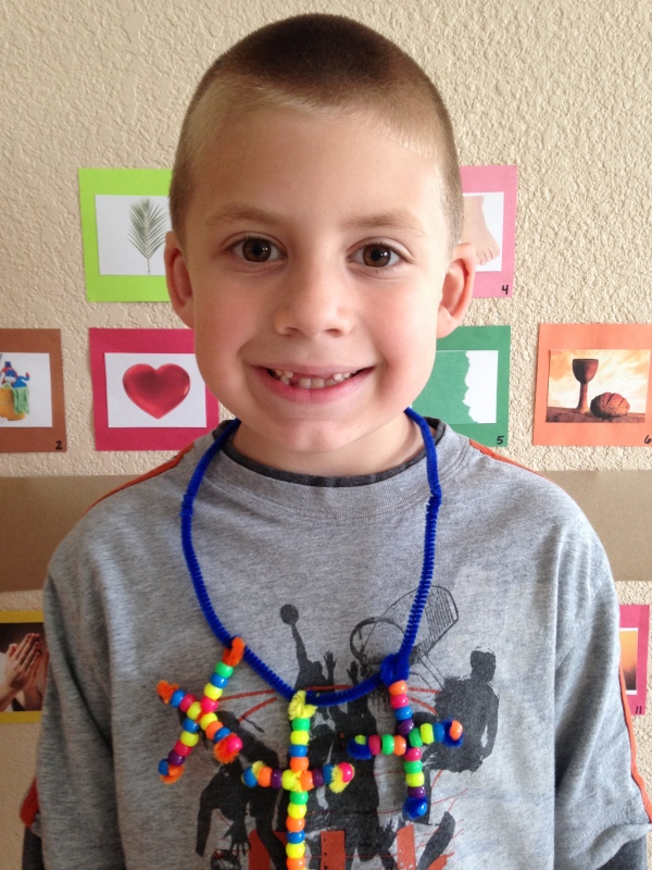 Jackson models his three cross bead necklace.