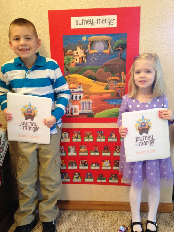 Jackson and Lauren hold their Journey to the Manger activity books in front of our Christmas Countdown board. Each day, we match a person (or animal) to the poster.