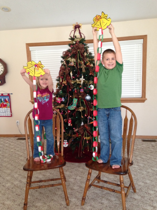 The kids hold their Christmas prayer chains high. Each day we will pray to our Father God for one person as we countdown to Jesus's birthday.