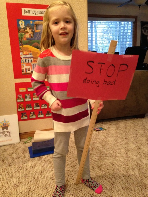 Lauren hold up the Red Light sign that holds the prophet Micah's message to the people of his day: Stop doing bad things!