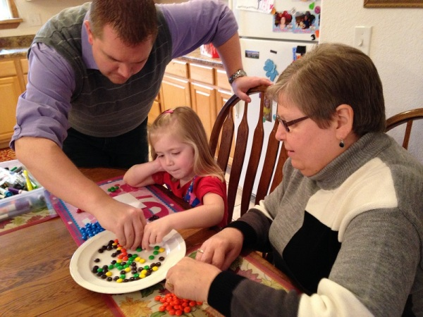 Daddy, Lauren and Grandma work to count their M&Ms in our census.