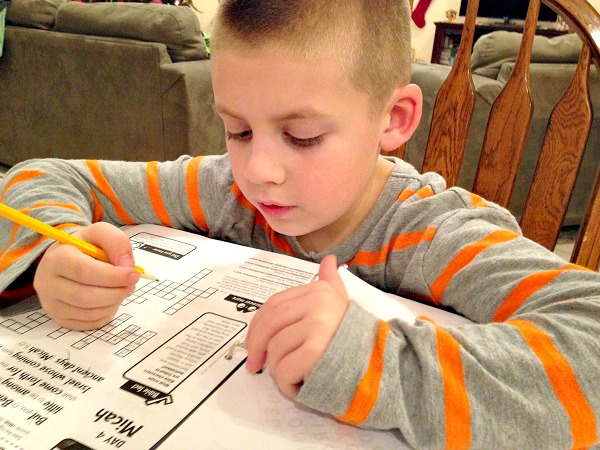 Jackson works on his puzzle page for Day 4 of Journey to the Manger.