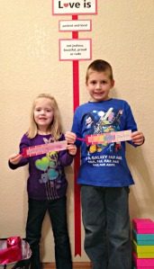 The kids stand in front of our Love Is wall hanging after Day 2, with bookmarks they made out of paint strip samples.